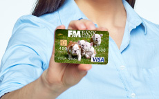 A close up on someone's hand holding an F&M debit card. The debit card has puppies on it.