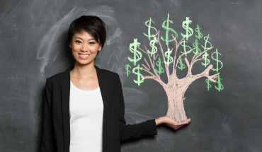 A woman smiling and standing against a chalkboard with a tree drawn on it.
