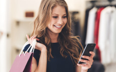 A young woman holding shopping bags and smiling while looking at her phone.