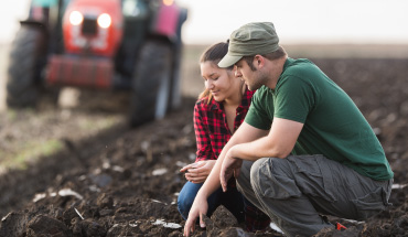 Two farmers kneeling in a field inspecting a spot in the soil