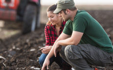 Two farmers kneeling in a field inspecting the soil.